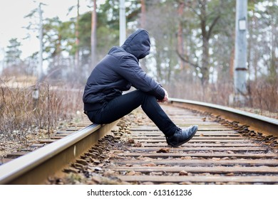 A lonely man sits on the railway, despair, autumn