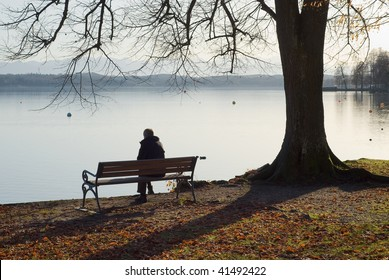Lonely Man Sitting Next to a Lake