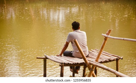 A lonely man sitting on the bamboo surface around a lake