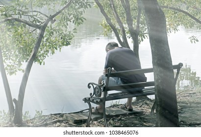 lonely man sitting on bench under tree in park with hopeless feeling in front of lake