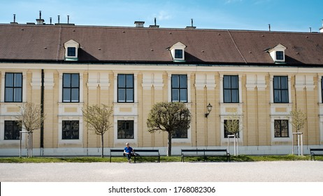 A lonely man is sitting on a bench at the vast, empty yard. a symmetric and powerful image, March 30th, 2019, Vienna, Austria.