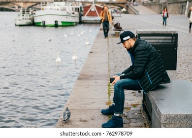 Lonely man sitting on bench in depression and thinking of problems in life. Abstract city background. Dove walking the embankment river in Prague. Psychological male portrait. Solitude and loneliness