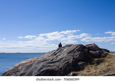 Lonely man sitting on the cliff in front of the sea