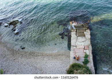 Lonely man sitting on a stone mole by the sea