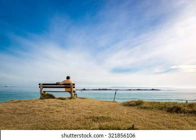 Lonely man sitting a public seat in front of a nice beach in a sunny blue sky day. Concept of dreaming, thinking, planning, looking forward...