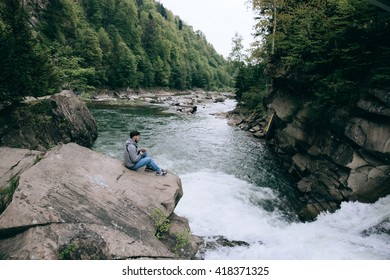lonely man sitting and relax on a rock waterfall mountain river