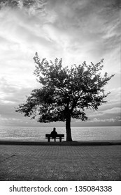a lonely man was sitting and thinking on the bench near sea side