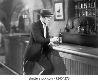 Lonely man standing at a bar counter with a drink