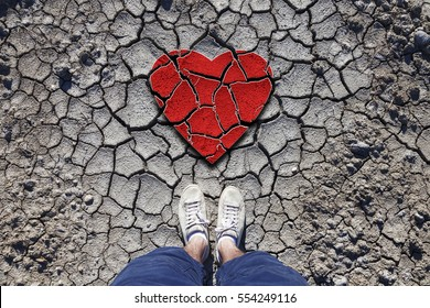 Lonely man standing on dried soil ground with illustrated cracked heart symbol. Conceptual broken love photo. Point of view perspective used.