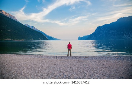 lonely man standing on the edge of beautiful Garda lake in the evening, Italy