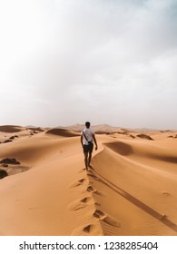 Lonely man stands in desert. Beautiful view of the dunes in the Sahara Desert, Morocco. Morning or evening Sun close to the horizon. Pure nature landscape