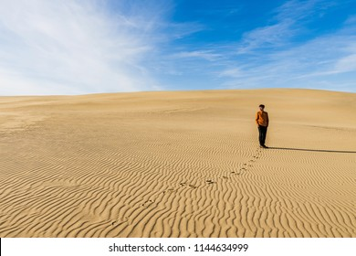 Lonely man stands in desert with footprints on the sand in sunny day. travel concept