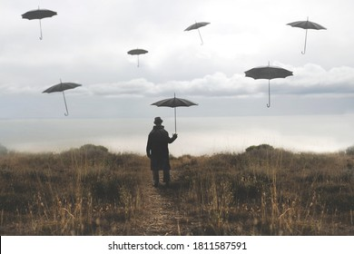 lonely man with umbrella walks down a road towards the lake and surreal black umbrellas fly in the sky