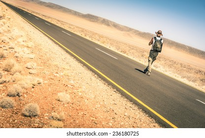 Lonely man walking along the road on namibian african desert - Alternative lifestyle concept and wanderlust experience with hipster guy backpacking to unknown - Travel trip adventure around the world