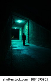 Lonely man walking in a dark alley at night. Danger and scary concept.