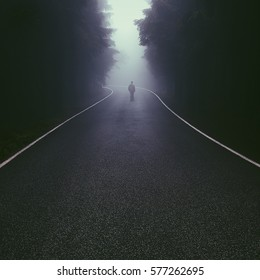 Lonely man walking down the foggy forest road