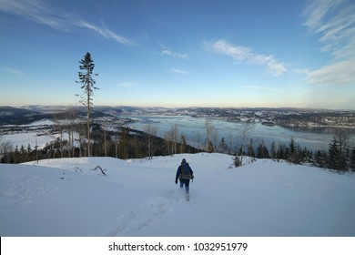 Lonely man walking down on background of Drammen fjord in winter time. Norway.