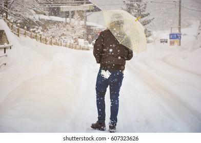 Lonely man walking and holding umbrella with snow falling background, Shirakawago, Japan