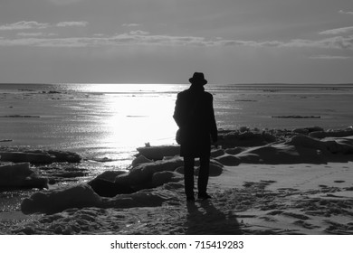 Lonely man walking on a beach black and white