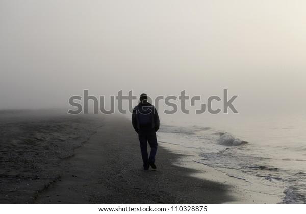 Lonely man walking on a foggy beach