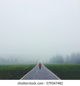 Lonely man walking the road disappearing in a fog