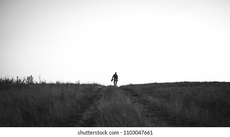 Lonely man walking through the field . Black and white photo.