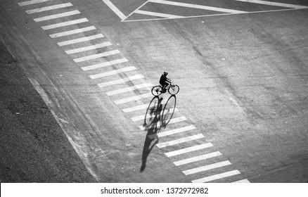 Lonely man wear helmet ride bicycle on street of Asian city, amazing long shadow of people on road surface take from high view in black and white, Ho Chi Minh city, Vietnam