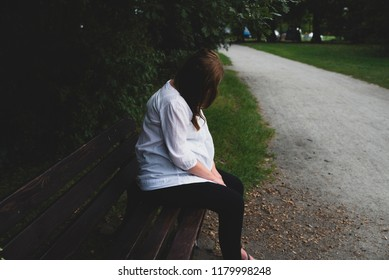 lonely mature pregnant woman in the park