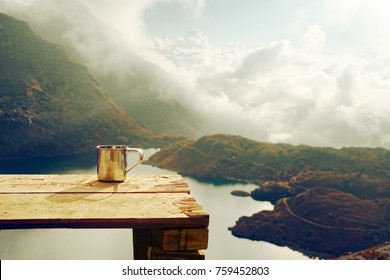 lonely metal cup on wooden table in the background of a mountain landscape at sunrise.