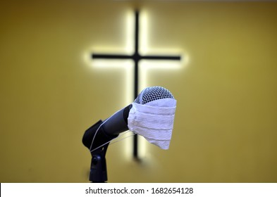 lonely microphone with mask in front of the cross