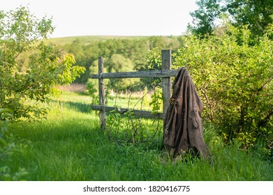 lonely military jacket with Soviet Army sign, hanging on rural garden fence in an abandoned place
