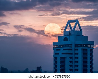 The lonely moment from a friendless guy looking at an abandoned building with giant moon behind. This is an supermoon phenomenon day in Bangkok city of Thailand.