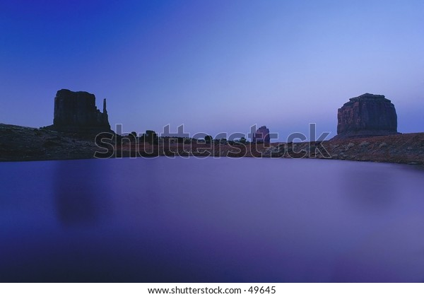 Lonely Monument. Monument valley at dusk with pond in foreground.