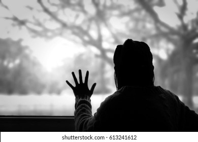 lonely mood - young woman looking out the window missing someone with black and white effect photography and black shadow