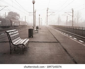 Lonely moody scene with a train station or railway platform on a foggy morning.