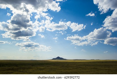 lonely mountain in yellow steppe under beautiful sky with white fluffy clouds, central Kazakhstan