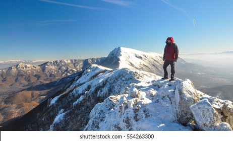 Lonely mountaineer get rest on snowy mountain high above the clouds into the sun