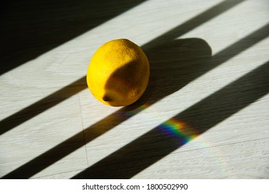 A lonely old lemon in partial shade and a rainbow lies on the laminate floor on a sunny day. Mental health concept. Copy space.  Hight contrast