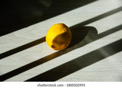A lonely old lemon in partial shade lies on the laminate floor on a sunny day. Mental health concept. Copy space.  Hight contrast.