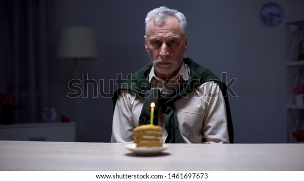 Lonely old man celebrating birthday alone, forgotten by children and relatives