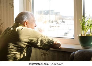 Lonely old man in an old-age home staring out of a window as he longs for his freedom and friends