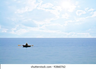 Lonely old man in the rowing boat on the sea