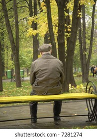 A lonely old man sitting on a bench in a park in Moscow among colorful autumn trees.