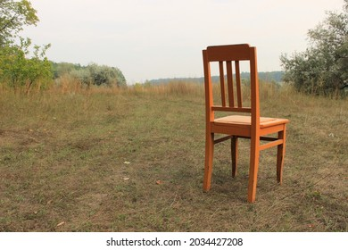 A lonely orange chair on the edge of the forest with copy space. A metaphor of exile from society.