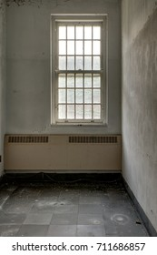 A lonely patient room with a wall heating unit and a barred window inside a derelict ward at a long abandoned hospital.