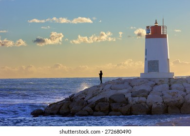 Lonely person in front of the sea on a sea wall near a small red and white lighthouse.
