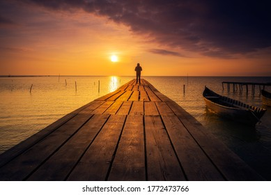 Lonely person standing on a pontoon meditating and enjoying the sunrise or sunset on a lake with a fishing boat on the lake