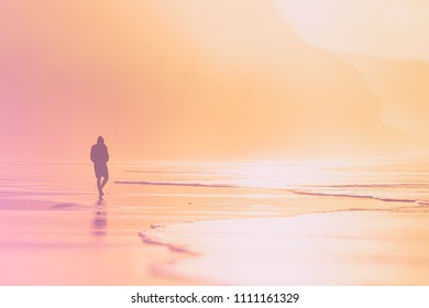 lonely person walking on beach at the sunset
