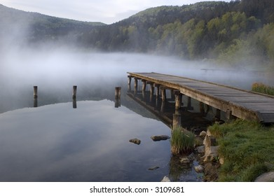 lonely pier on lake in early morning