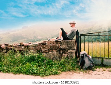 Lonely Pilgrim with backpack resting. Camino de Santiago, Camino del Norte or the Coastal Saint James Way, pilgrimage route along the Northern coast of Spain